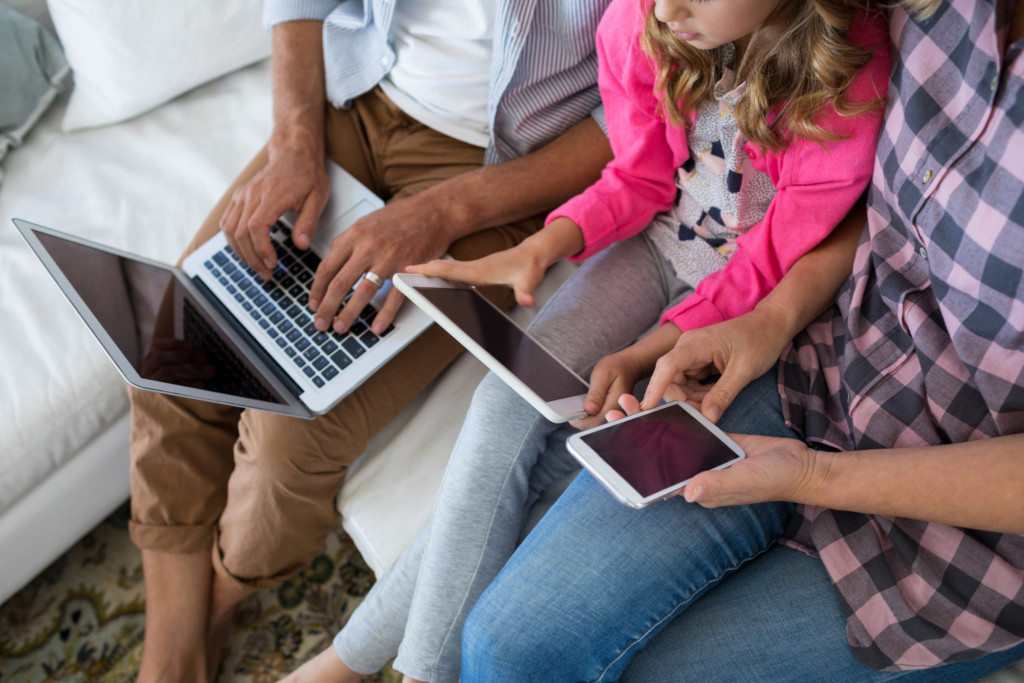 Family using laptop, digital tablet mobile phone THE FAMILY IS WIRED. NOW WHAT? Parenting in the Digital Age Gina Hickey Contributor Miami Moms Blog