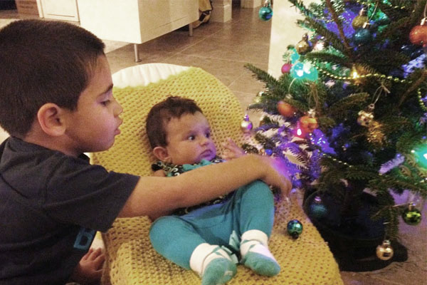 little boy and baby girl next to tiny christmas tree