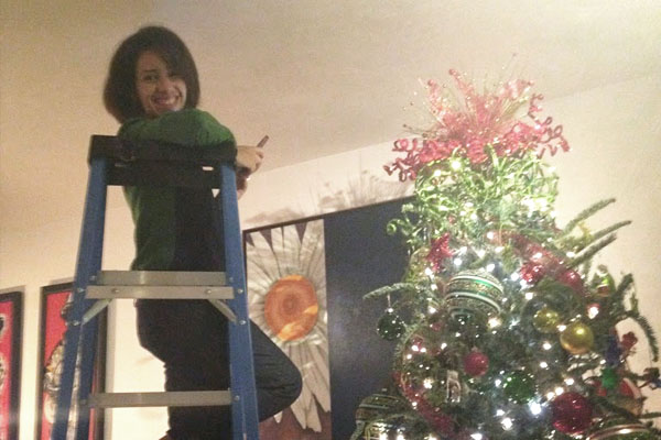 women in ladder next to top of christmas tree