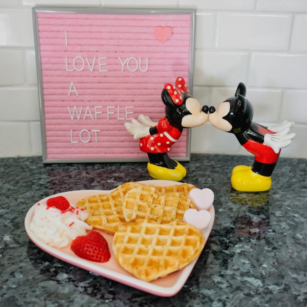 """""""I love you a waffle lot"""" sign with Mickey Mouse & Minnie Mouse, and a plate of heart-shaped waffles (Valentine's Day: Fun, Family-Friendly Ideas Becky Salgado Contributor Miami Mom Collective)"""