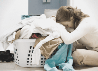 An overwhelmed mom leaning over a basket of laundry (A Letter to Moms as We Stumble Into 2021: There is Hope by Lindsay K. Madsen, Miami Mom Collective)