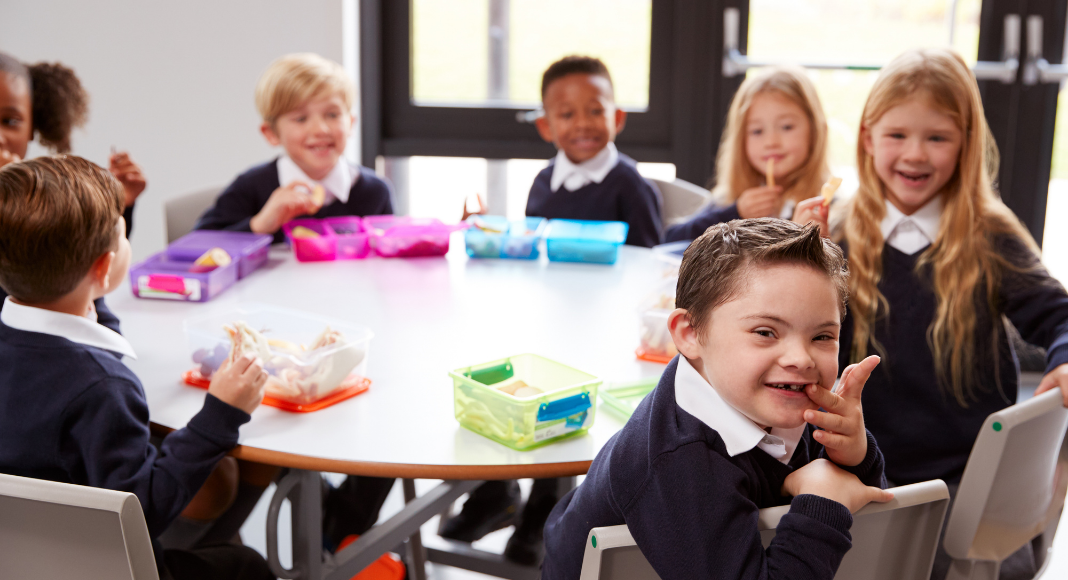Raising Inclusive Kids -Image Description: several diverse children sit together at a school table for lunch
