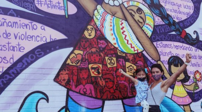 Ana with her daughter in front of a colorful street mural (International Women's Day: This Year, #ChooseToChallenge Ana Caballeros Contributor Miami Mom Collective)