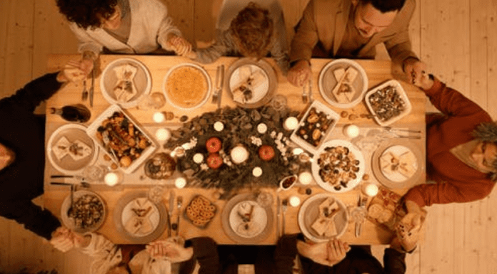 A large family gathered around the dinner table (Family Mealtime is the Heart of the Home Holly Farver Contributor Miami Mom Collective)