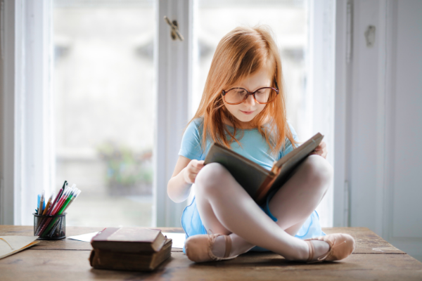 A little girl with a book (Lorena Lougedo Contributor Miami Mom Collective)