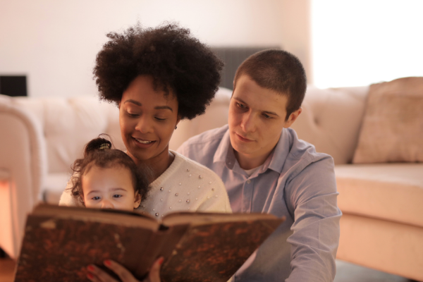 A family looking at a book together (Lorena Lougedo Contributor Miami Mom Collective)