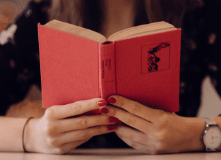 A woman holding an open book (Let's Celebrate: National Reading Across America Day Lorena Lougedo Contributor Miami Mom Collective)