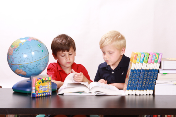 Two classmates looking at an encyclopedia (Let's Celebrate: National Reading Across America Day Lorena Lougedo Contributor Miami Mom Collective)