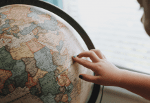 A little girl looking at a globe (Tooth Fairy Traditions From Around The World | Dr. Bob Pediatric Dentist Lynda Lantz Contributor Miami Mom Collective)