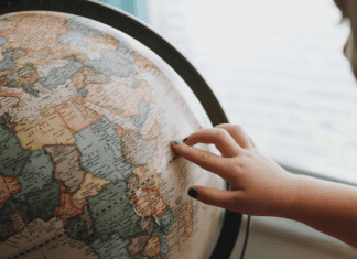 A little girl looking at a globe (Tooth Fairy Traditions From Around The World   Dr. Bob Pediatric Dentist Lynda Lantz Contributor Miami Mom Collective)