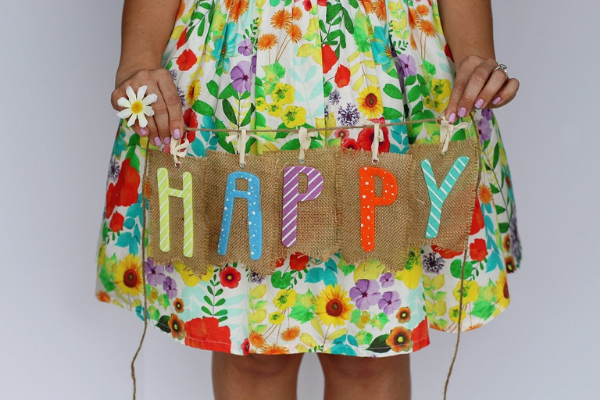 """A little girl holding a sign that says """"Happy"""" (Jessica Alvarez-Ducos Contributor Miami Mom Collective)"""