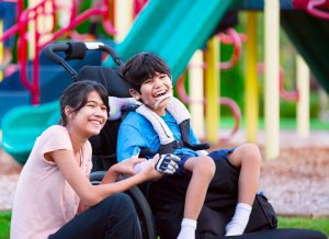 Raising Inclusive Kids -Image Description: A boy and a girl are in front of a playground. The girl is able-bodied and the boy is sitting in a wheelchair.
