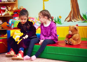 Raising Inclusive Kids -Image Description: Two girls are sitting together in a brightly colored room. One girl is wearing adaptive shoes and appears to have a physical disability.