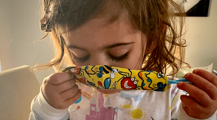 A toddler putting a mask on (Wear a Mask: How To Get Your Toddler to Wear One (and Keep It On!) Alexa Gonzalez Contributor Miami Mom Collective)