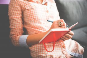 A woman journaling (Stress Awareness Month: The Importance of Checking in With Yourself Rachelle Haime Contributor Miami Mom Collective)