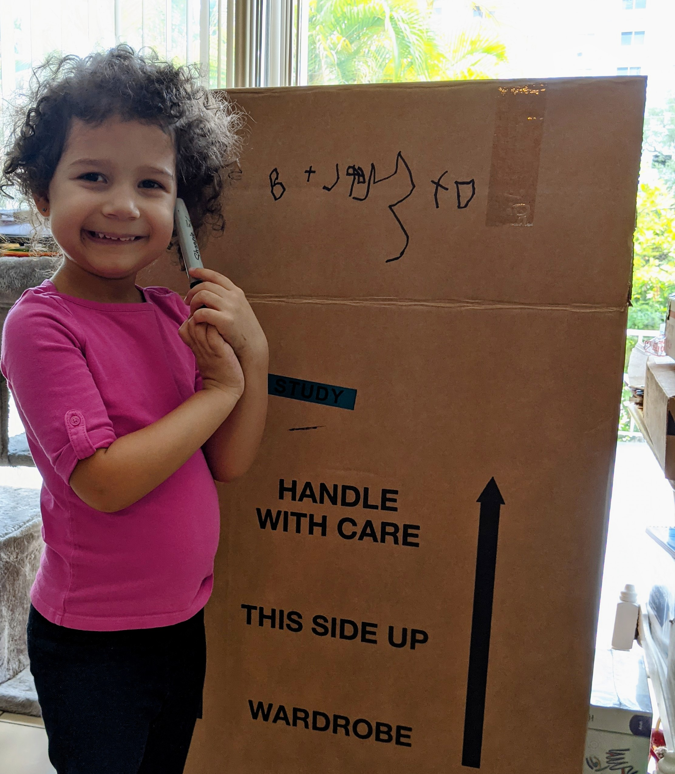 Lynda's daughter smiling next to a moving box (Dental Emergencies: Keep Calm & Call Dr. Bob Lynda Lantz Contributor Miami Mom Collective)