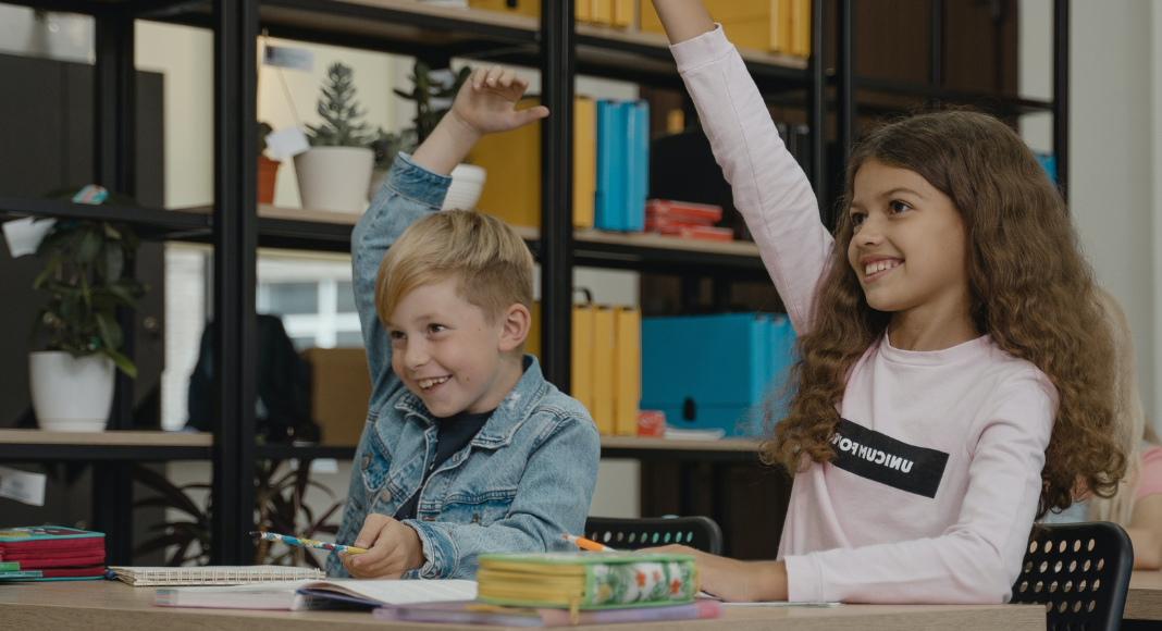 Two students raising their hands (Get Involved: 3 Ways to Help Your Student Succeed Ailyn Quesada Contributor Miami Mom Collective)