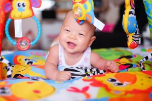 Image Description: a baby is smiling while doing tummy time on a brightly colored mat. Colorful toys are hanging from a play gym in front of the baby. (Tummy Time Without Tears: Tips From a Pediatric Physical Therapist Brittany Aquart Contributor Miami Mom Collective)