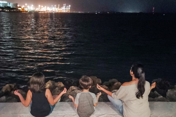 Minnie and her kids sitting by the water (Minerva Roca Contributor Miami Mom Collective)