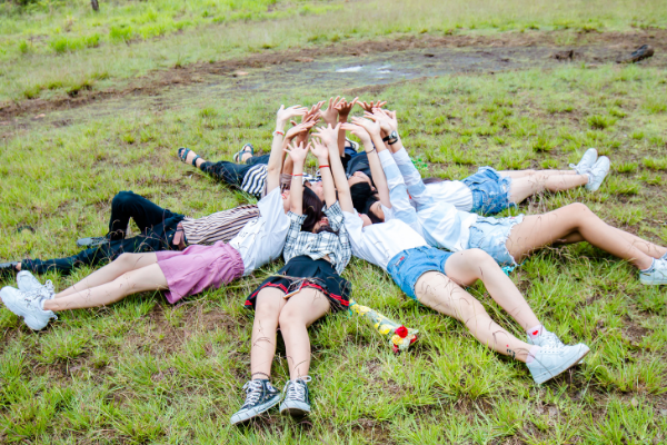 A group of people lying out in the grass (Fighting Summer Boredom Lorena Lougedo Contributor Miami Mom Collective)