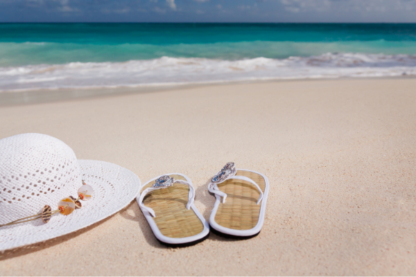 Flip flops and a sun hat on the sand (Lorena Lougedo Contributor Miami Mom Collective)