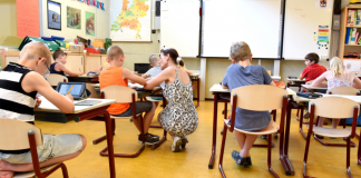 A teacher helping a student in a classroom (Teacher Appreciation Week: Let's Show Appreciation Lorena Lougedo Contributor Miami Mom Collective)