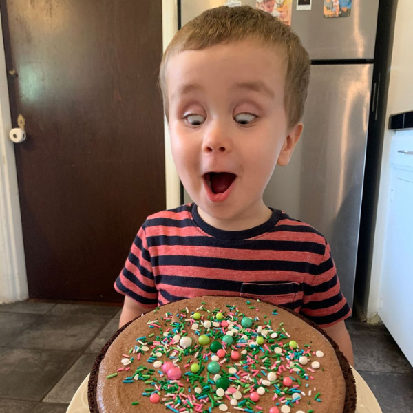 """""""How I Went Gluten-Free"""" Image: a young boy in a striped shirt looks down excitedly at a chocolate cake with sprinkles. (How I Went Gluten-Free Brittany Aquart Contributor Miami Mom Collective)"""