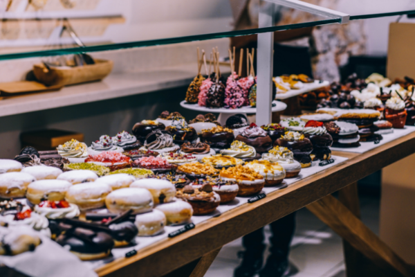 A bakery counter full of donuts and sweet treats (National Donut Day: Make it A-Glaze-ing! Ana-Sofia DuLaney Contributor Miami Mom Collective)