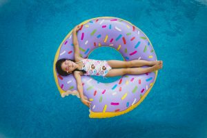 A little girl on a donut shaped inner tube (Summer 2021 Parties Made Easy Aymee Blanco Contributor Miami Mom Collective)