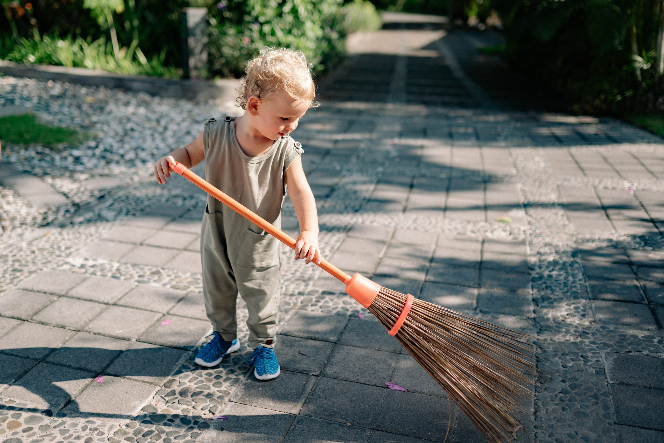 A toddler sweeping (Summer Fun that Leads to Lasting NEW Habits for the Entire Family Adita Lang Contributor Miami Mom Collective)
