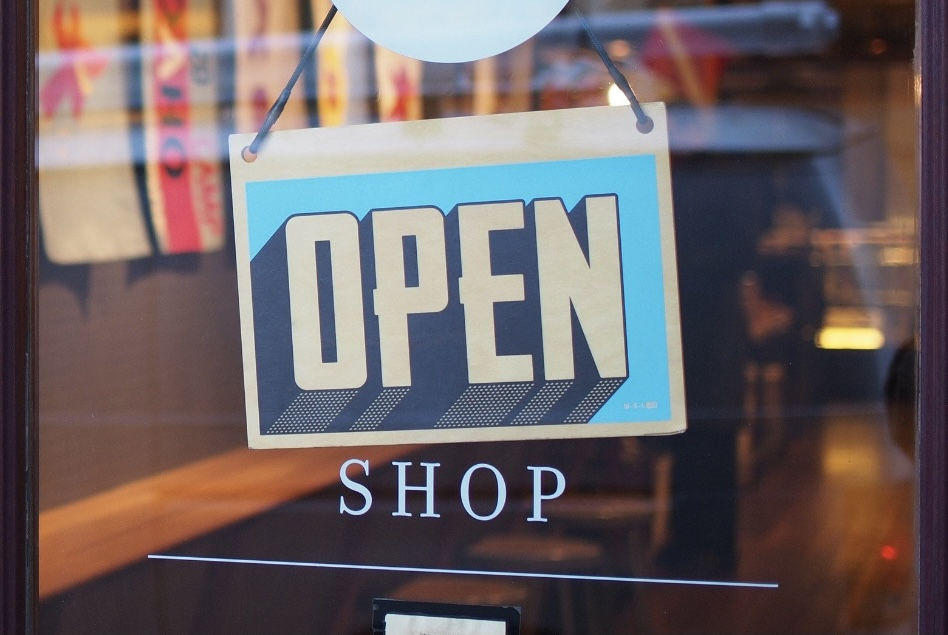 """An """"OPEN"""" sign on the front door of a local business (August is Black Business Month: 3 Ways to Support Black Businesses Sharonda Stewart Contributor Miami Mom Collective)"""
