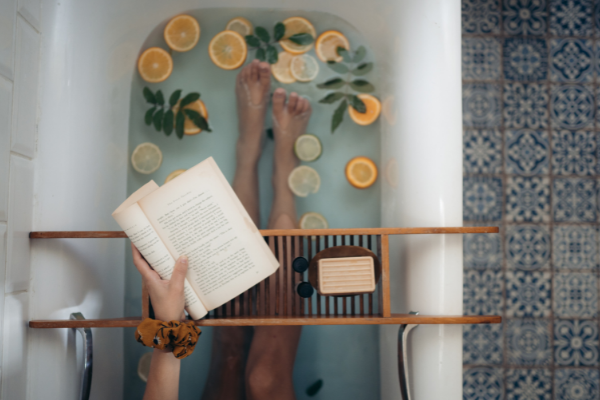 Reading a book in the bath (Summer Reading List for Moms Krystal Giraldo Contributor Miami Mom Collective)
