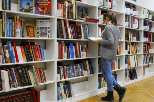 A woman browsing in a bookstore (Summer Reading List for Moms Krystal Giraldo Contributor Miami Mom Collective)