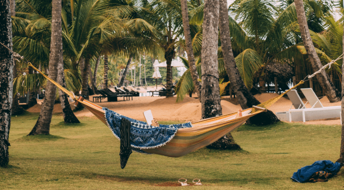 A woman in a hammock reading a book (Summer Reading List for Moms Krystal Giraldo Contributor Miami Mom Collective)