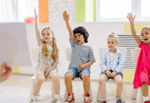 A group of children raising their hands (Your Child Votes YES! Getting Involved at Your Child's School Matters! Holly Farver Contributor Miami Mom Collective)