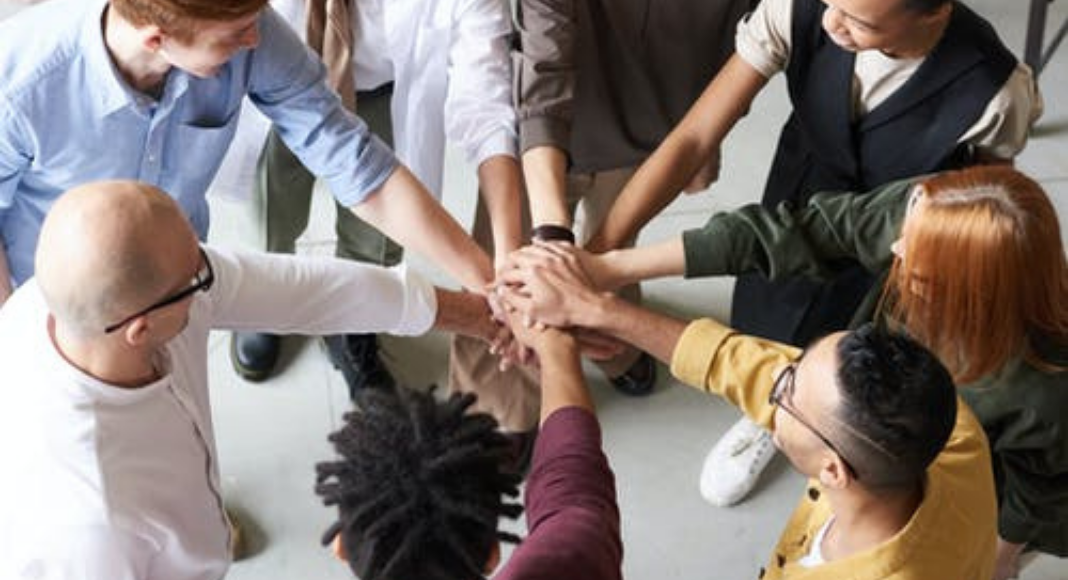 A group of people in a huddle (Your Child Votes YES! Getting Involved at Your Child's School Matters! Holly Farver Contributor Miami Mom Collective)