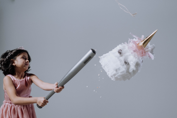 A girl hitting a pinata (Hispanic Heritage Month: Ways to Celebrate Lorena Lougedo Contributor Miami Mom Collective)