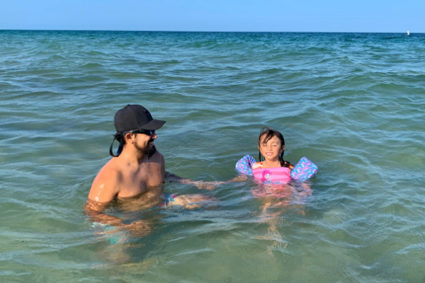 Jessica's daughter playing in the ocean with her dad (Beach More, Stress Less : Beach Day Tips and Hacks Jessica Alvarez-Ducos Contributor Miami Mom Collective)