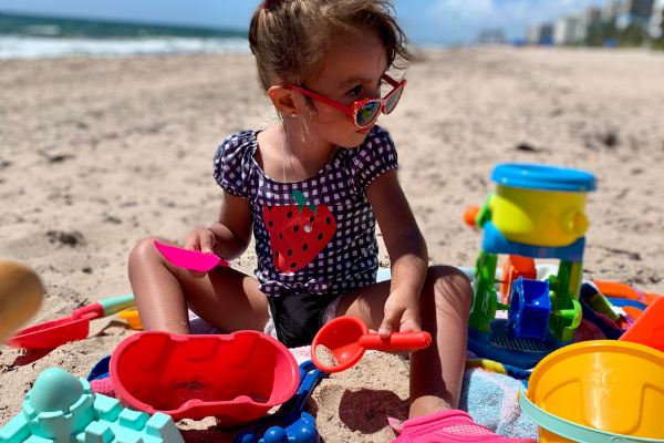 Jessica's daughter playing with sand toys at the beach (Beach More, Stress Less : Beach Day Tips and Hacks Jessica Alvarez-Ducos Contributor Miami Mom Collective)