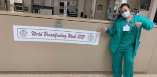 A nurse posing next to a banner for World Breastfeeding Week (World Breastfeeding Week: Raising Global Awareness Alexa Gonzalez Contributor Miami Mom Collective)