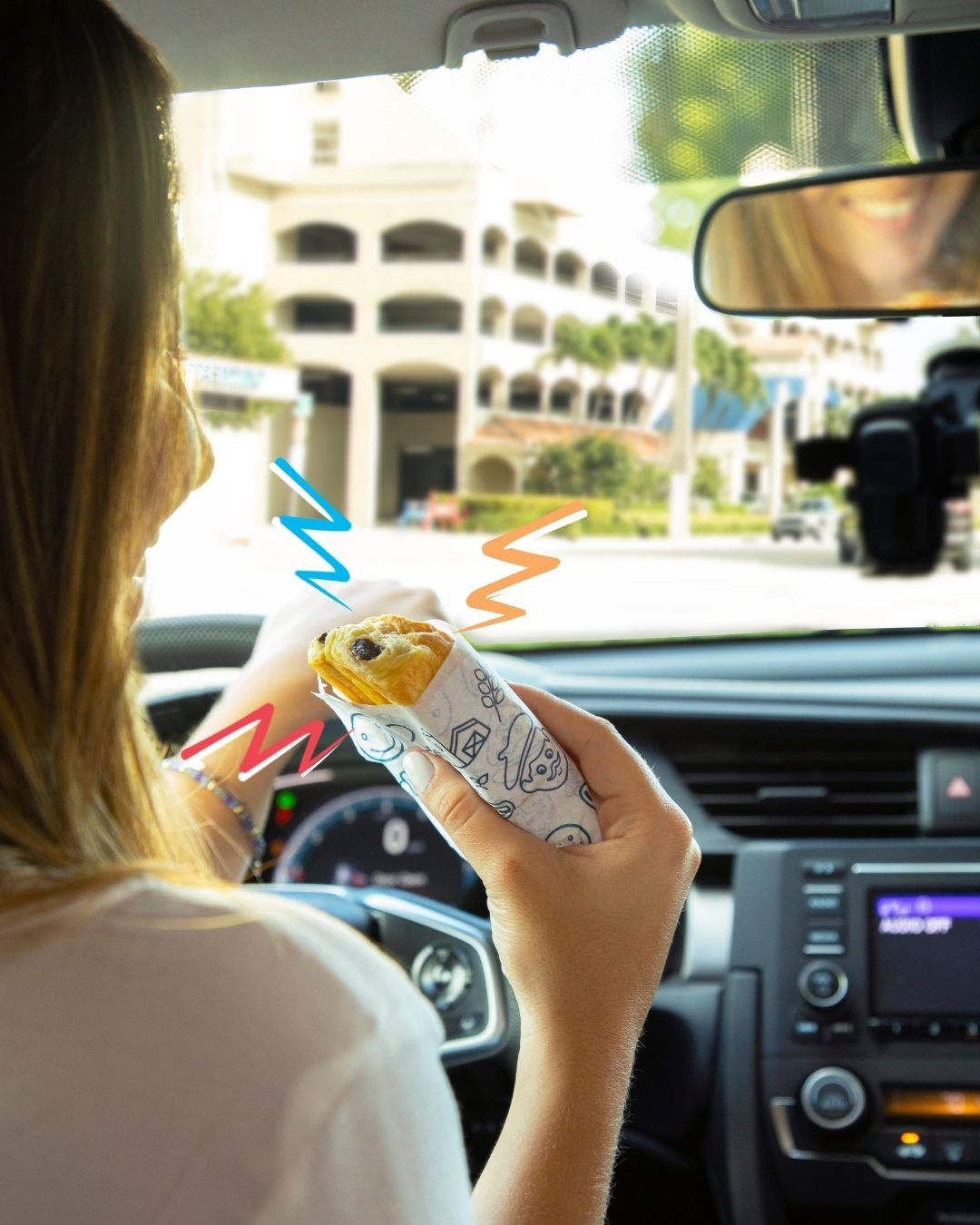 A woman eating a chocolate croissant from bakerly in the car (Snack Time: Unwrap et Voilà With These Snacks From Bakerly Lynda Lantz Contributor Miami Mom Collective)