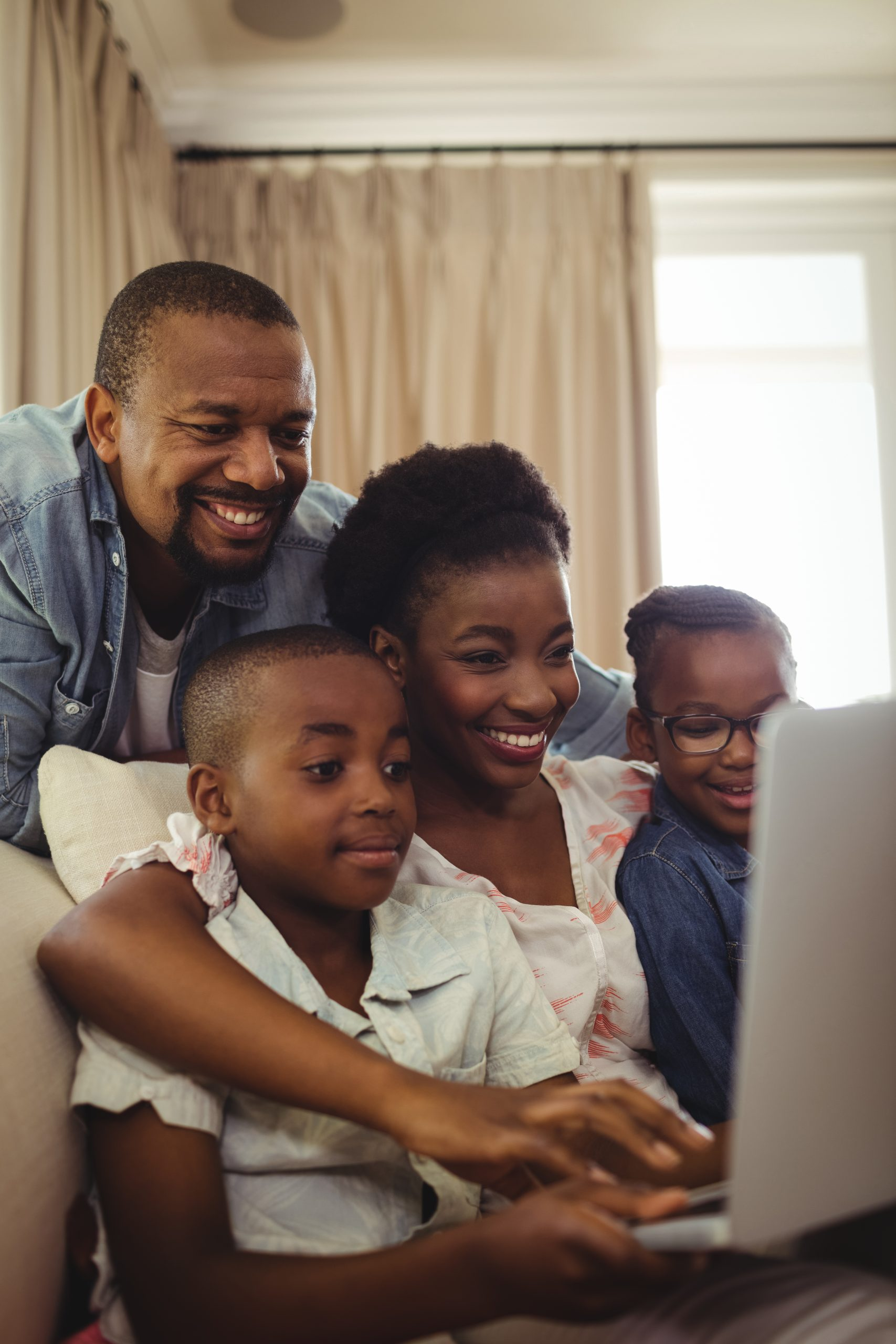 A family using a computer together (Kids and Tech: Back to School in a Pandemic Be Strong International Miami Mom Collective)