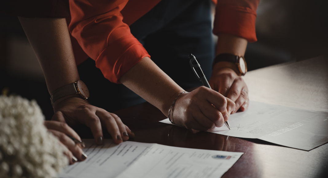 A couple signing documents (Designation of Health Care Surrogate for A Minor: What You Should Know Kristina Hernandez Tilson Contributor Miami Mom Collective)