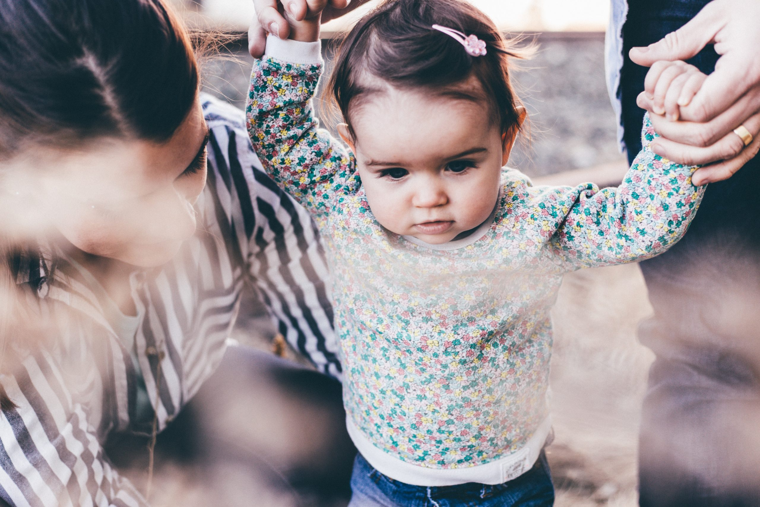 Parents helping their toddler take steps (Designation of Health Care Surrogate for A Minor: What You Should Know Kristina Hernandez Tilson Contributor Miami Mom Collective)