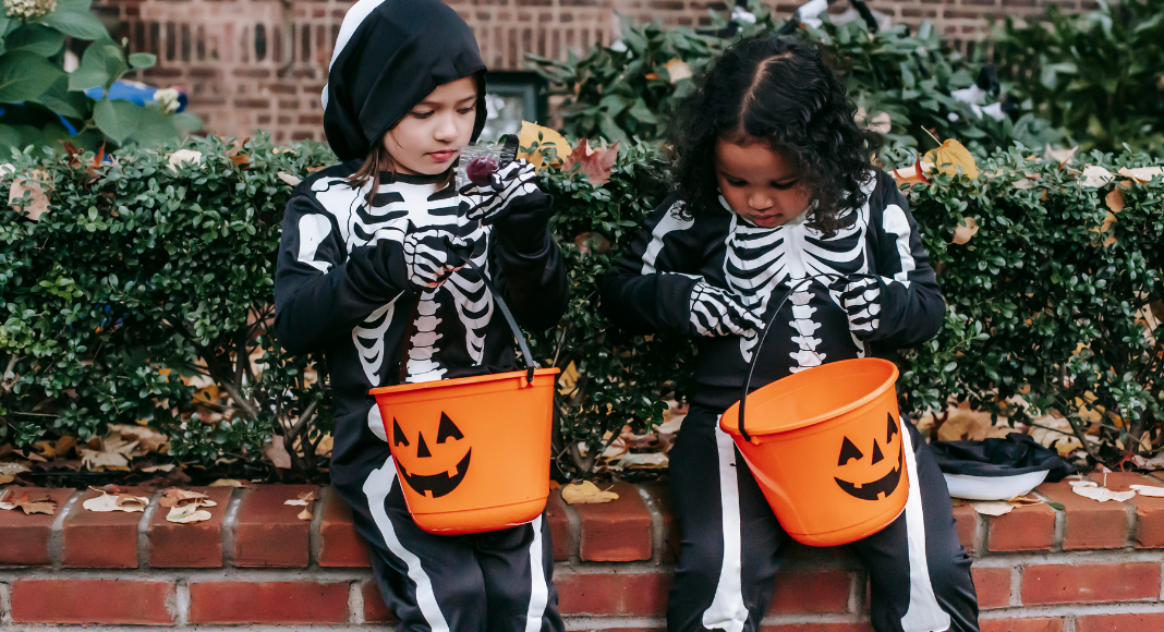 Image: Two girls in skeleton costumes sitting with their Halloween buckets (Allergy-Friendly Halloween: Tricks and Treats Monica Moreno Contributor Miami Mom Collective)