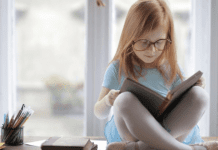 Image: A little girl reading a book (October is Dyslexia Awareness Month Sharonda Stewart Contributor Miami Mom Collective)